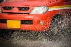 Arrosez l'éclaboussure avec la voiture sur la route inondée après des pluies Photo stock