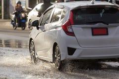 Arrosez l'éclaboussure avec la voiture sur la route inondée après des pluies Images stock
