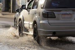 Arrosez l'éclaboussure avec la voiture sur la route inondée après des pluies Images libres de droits