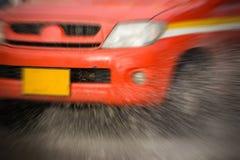 Arrosez l'éclaboussure avec la voiture sur la route inondée après des pluies Image stock