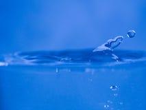 Arrosez l'éclaboussure dans la couleur bleue avec une baisse sortant de l'eau Images stock