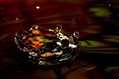 Arrosez l'éclaboussure en couleurs avec une goutte de l'eau Images stock