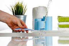 Arrosez l'éclaboussure sur la brosse à dents par le jet d'eau dans la salle de bains Images stock