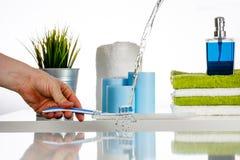 Arrosez l'éclaboussure sur la brosse à dents par le jet d'eau dans la salle de bains Photos libres de droits