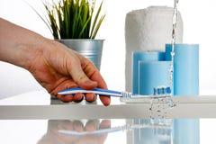 Arrosez l'éclaboussure sur la brosse à dents par le jet d'eau dans la salle de bains Image libre de droits