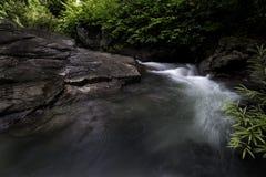 Arrosez l'entrée au-dessus des grandes roches dans la forêt de cascade Photos libres de droits