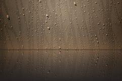 Arrosez la baisse sur le mur brun avec le reflction Image libre de droits