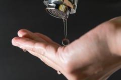 Arrosez la baisse sur le robinet avec les milieux noirs, concept de jour de l'eau du monde Photo libre de droits