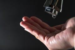 Arrosez la baisse sur le robinet avec les milieux noirs, concept de jour de l'eau du monde Images stock