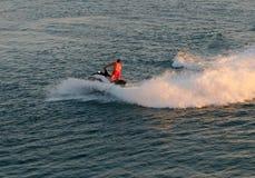 Arrosez la moto avec un homme sur les vagues images libres de droits
