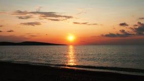Arrosez la surface de couleur d'or au bord de la mer au coucher du soleil banque de vidéos
