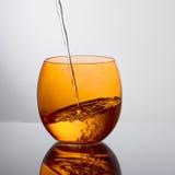 Arrosez le versement dans le beau verre orange de couleur boisson images libres de droits