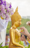 Arrosez le versement et la statue dorée de Bouddha dans le festival de Songkran traditionnel Photos libres de droits