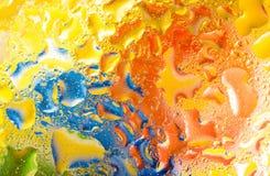 Arrosez les baisses sur le verre avec le fond orange vert-bleu Photographie stock libre de droits