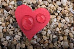Arrosez les baisses sur un papier en forme de coeur sur le sable Photographie stock libre de droits