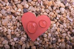 Arrosez les baisses sur un papier en forme de coeur sur le sable Photos stock