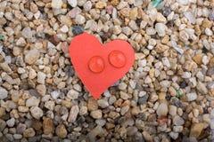 Arrosez les baisses sur un papier en forme de coeur sur le sable Images libres de droits