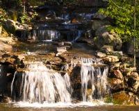 Arrosez les cascades au-dessus des roches et dans une piscine photos stock