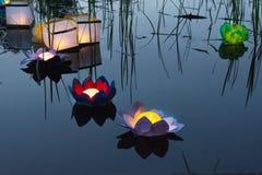 Arrosez les lanternes jaunes brûlantes sur le lac parmi l'herbe grande Image stock