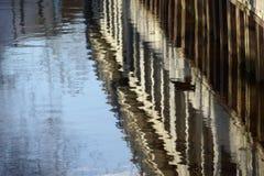 Arrosez les réflexions de la palplanche et des bâtiments commerciaux i photographie stock