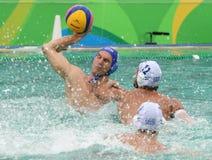 Arrosez Polo Team Hungary dans le bleu et Team Greece dans l'action pendant le match rond préliminaire du groupe A du ` s d'homme Photo libre de droits