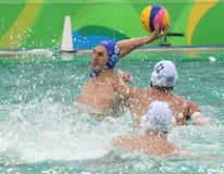 Arrosez Polo Team Hungary dans le bleu et Team Greece dans l'action pendant le match rond préliminaire du groupe A du ` s d'homme Image stock