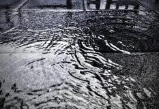 Arrosez sur la rue à l'arrière-plan de saison de pluie de jour pluvieux Photos stock