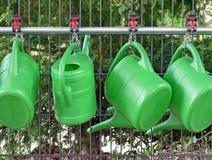 Arrosoirs en plastique verts sur un cimetière, Allemagne Image stock