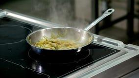 Arrostendo e cucinando carne in una padella archivi video