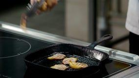 Arrostendo e cucinando carne in una padella video d archivio