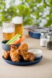 Arrostisca col barbecue le ali di pollo calde con le birre al giardino del pub Fotografie Stock