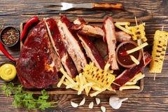 Arrostisca col barbecue le costole di carne di maiale, le patate fritte e le pannocchie di granturco fotografia stock