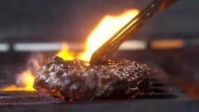 Arrostisca la carne per la vibrazione dell'hamburger sulla griglia video d archivio