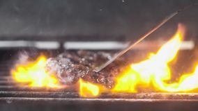 Arrostisca la carne per la vibrazione dell'hamburger sulla griglia Movimento lento, primo piano video d archivio