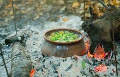 Arrostisca in un vaso di argilla sul fuoco Immagini Stock
