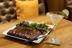 arrosto di carne di maiale del ribeye e Magarita Fotografia Stock