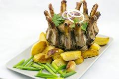 Arrosto di corona di carne di maiale con i cunei della patata fotografie stock