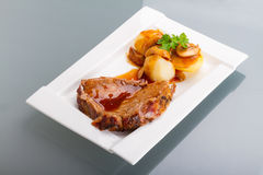 Arrosto di maiale con sugo e le patate Fotografia Stock Libera da Diritti