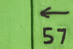 Arrow 57. Graffiti on the green textured wall royalty free stock photo