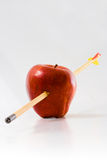 Arrow Through an Apple. Arrow piercing an apple, isolated on white background - full focus Stock Image