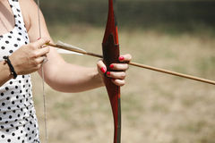 Arrow and bow in hands of an unidentified archer Royalty Free Stock Photo