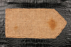 Arrow of burlap, lies on a background of crocodile  leather Royalty Free Stock Photography