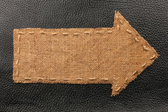 Arrow of burlap, lies on a background of leather Stock Images