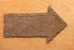 Arrow of burlap  lies on wooden  background Stock Images