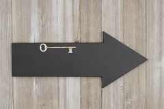 Arrow chalkboard sign with a skeleton key on weathered wood Stock Photo