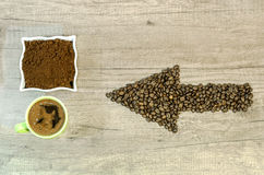 Arrow from the coffee beans with a cup of fresh ground coffee and full green cup Royalty Free Stock Images