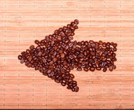 Arrow of coffee beans on a decorative straw Stock Images