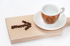Arrow of coffee beans and empty cup of coffee Stock Image