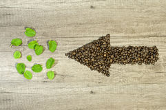 Arrow from the coffee beans with mint tea leaf wooden background Stock Photos