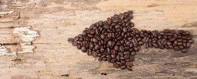 Arrow from the coffee beans on wood Stock Image